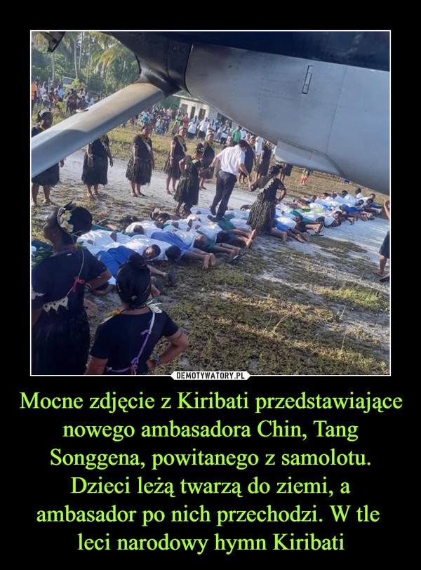 Mocne zdjęcie z Kiribati przedstawiające nowego ambasadora Chin, Tang Songgena, powitanego z samolotu. Dzieci leżą twarzą do ziemi, a ambasador po nich przechodzi. W tle leci narodowy hymn Kiribati –